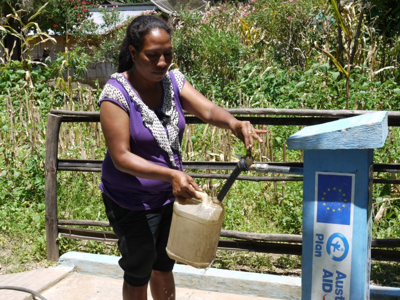 Emilia uses water pump installed by Plan International