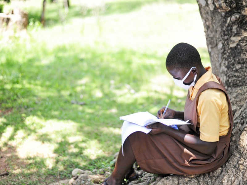 Girl writes a letter under a tree while wearing a mask