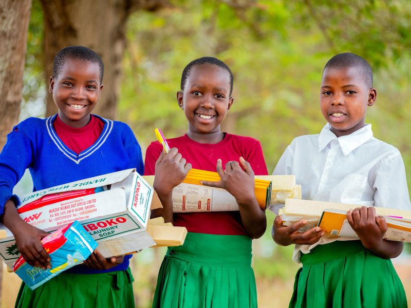 Girls holding supplies in Tanzania, 2020.