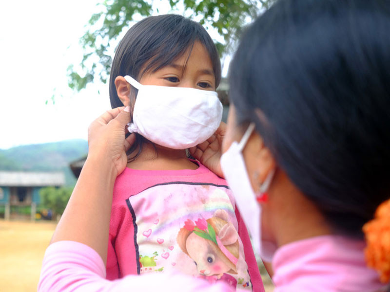 Mother puts face a face mask on her young daughter in, Vietnam.