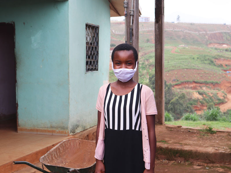 Young girl, wearing a stripped black and white top and baby pink cardigan, wearing a face mask.