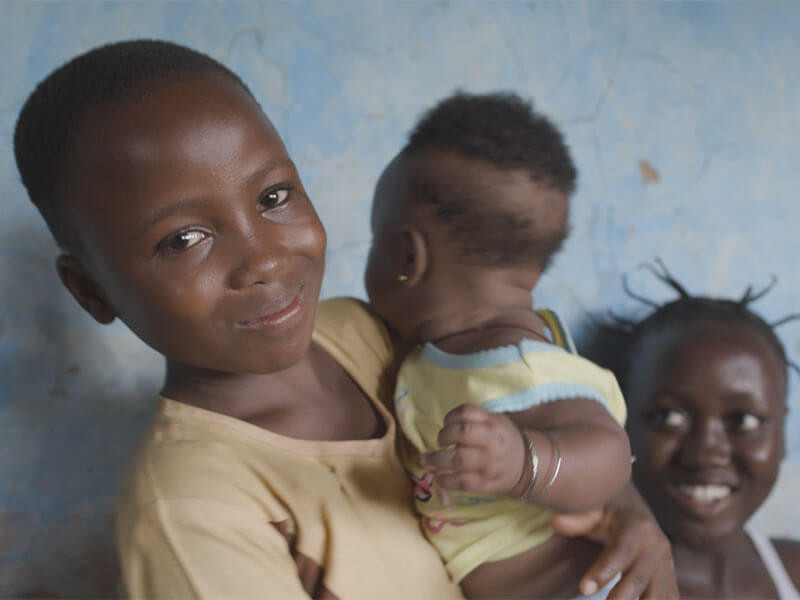 Child Smiling holding a baby, Ghana