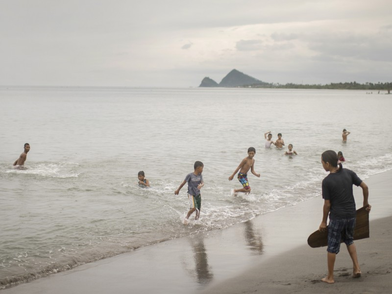 children play in the sea again a year after the typhoon