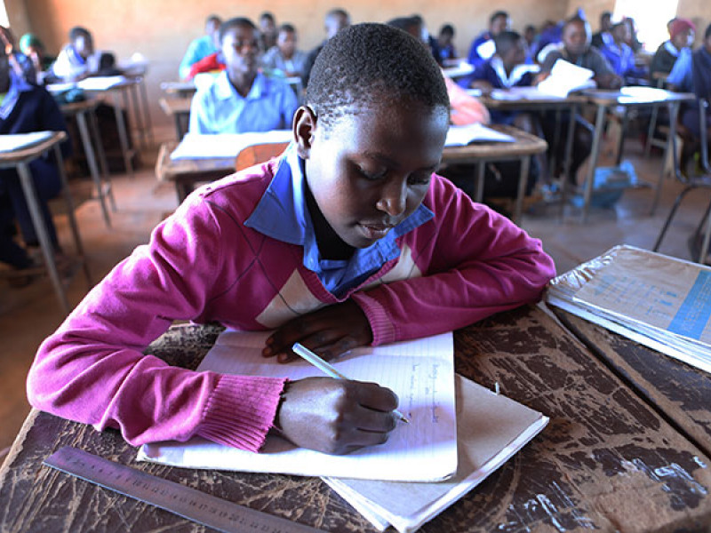 A girl at her desk in a busy classroom