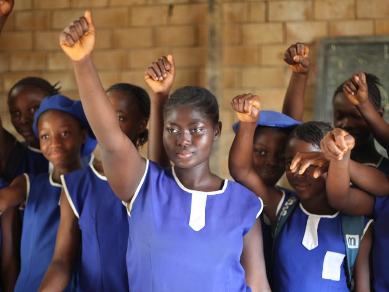 girls raise their hands against FGM