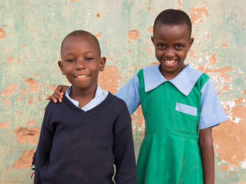 Lucia and Nzioki standing proudly in their school uniform