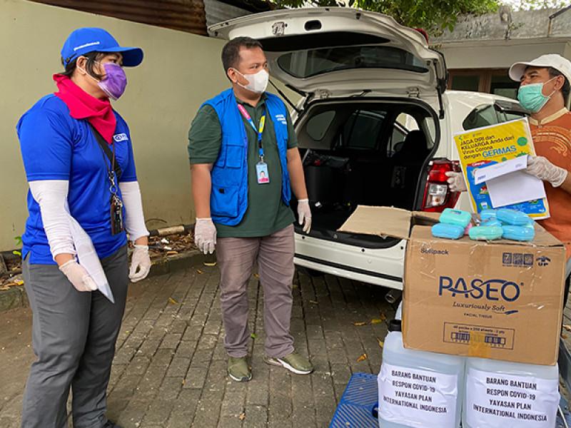 Plan International staff distribute hand sanitiser and soap