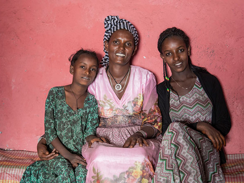 A mum sits with her two daughters