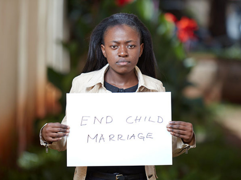 Photo of a girl holding a sign saying 'End child marriage'