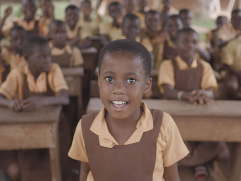 Sarah standing up in front of her friends, Ghana