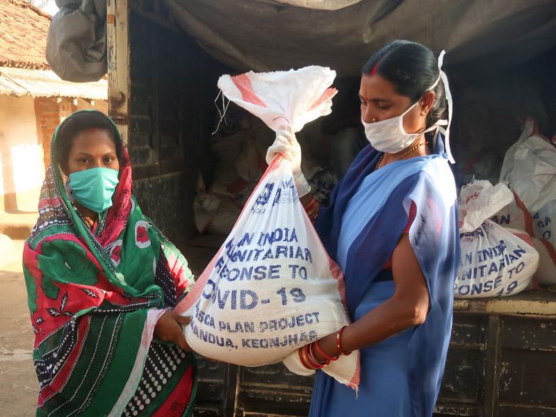 A woman receives food odisha state, India, covid-response.