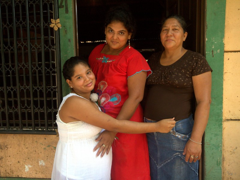 pregnant girl with her mother and grandmother outside her home in Nicaragua