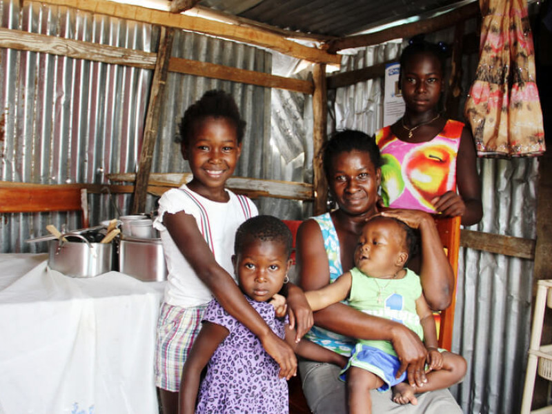 A family in a temporary shelter constructed with help from Plan International in Haiti