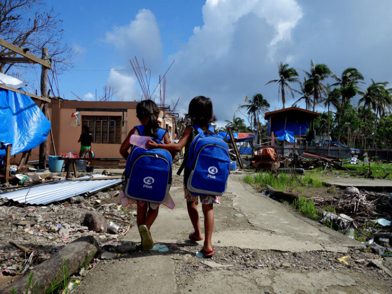Two girls with backpacks from Plan after Typhoon Haiyan