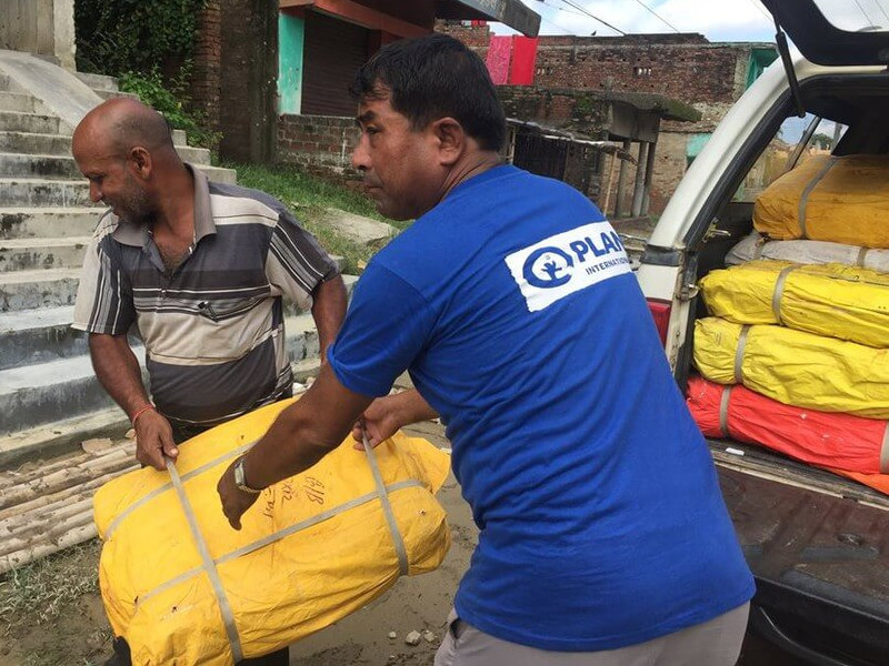 Plan International response team distributing food and materials to flood affected families