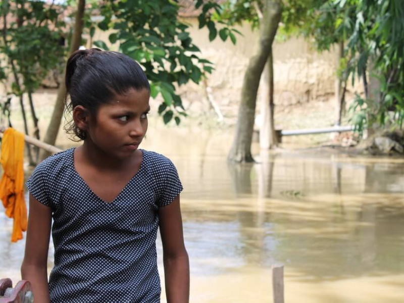 Manisha overlooks the flooding that damaged her home in Nepal