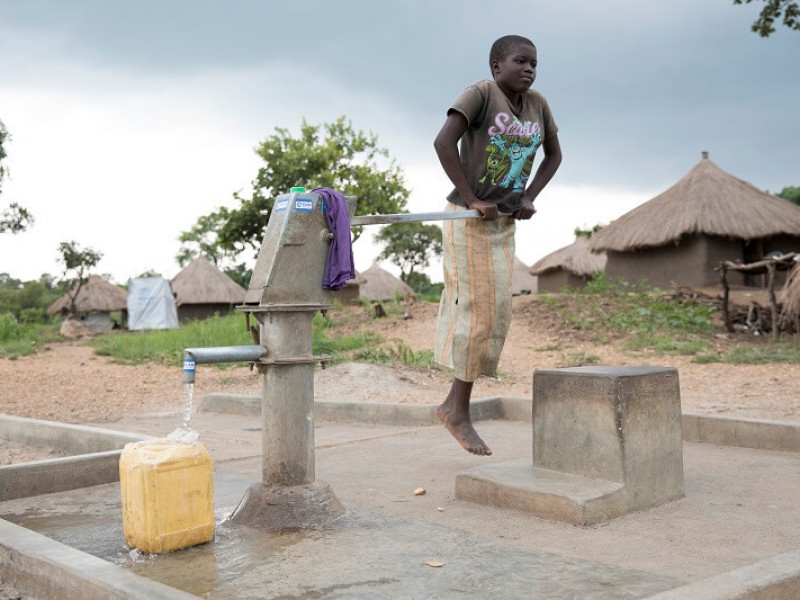 A girl pumping water in a refugee settlement in Uganda