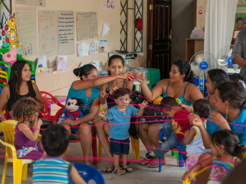 Mothers play games with children at a child-friendly space in Ecuador