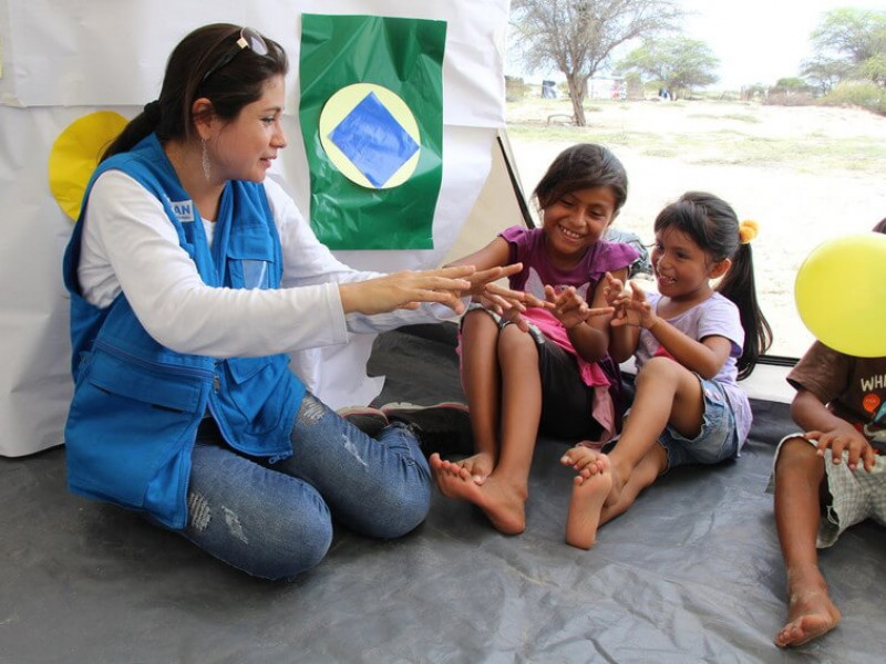 A Plan International staff member plays with girls at a temporary shelter