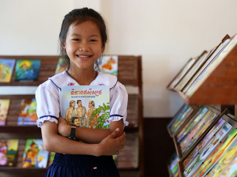 A child reads at a Plan-supported library in Cambodia