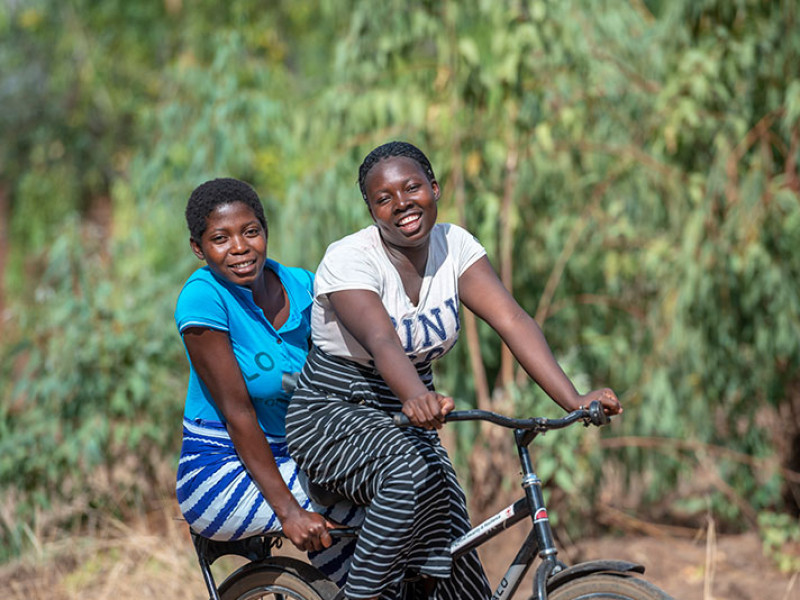 Two adolescent girls on a bike in rural Malawi