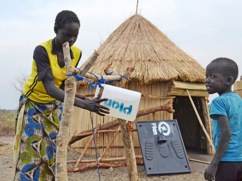 Refugee camp resident in Uganda using a water station