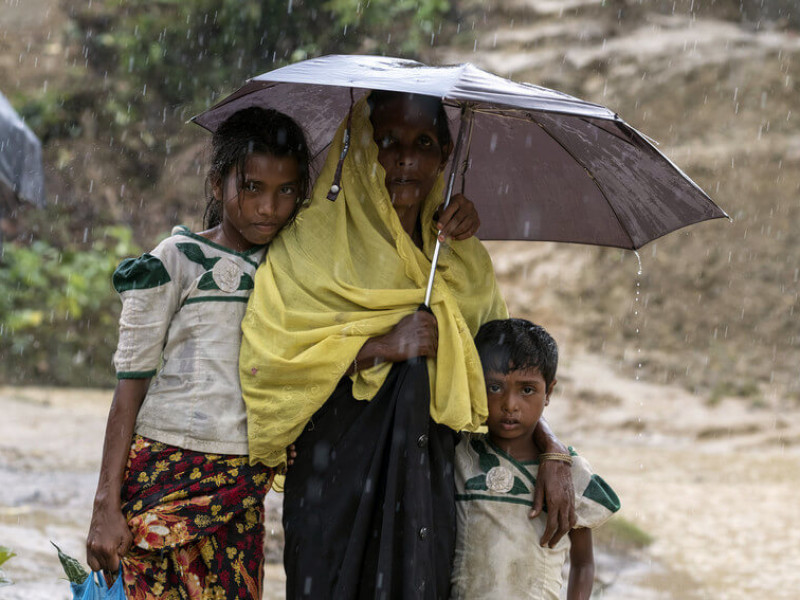 A woman and children sheltering from rain in Balukhali camp in Bangladesh