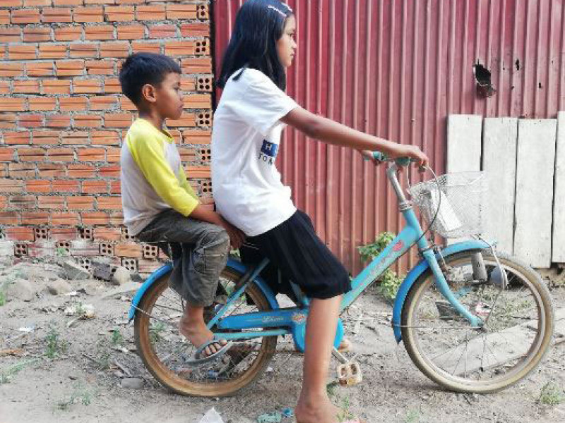 Cycling with her sibling in Cambodia, 2018