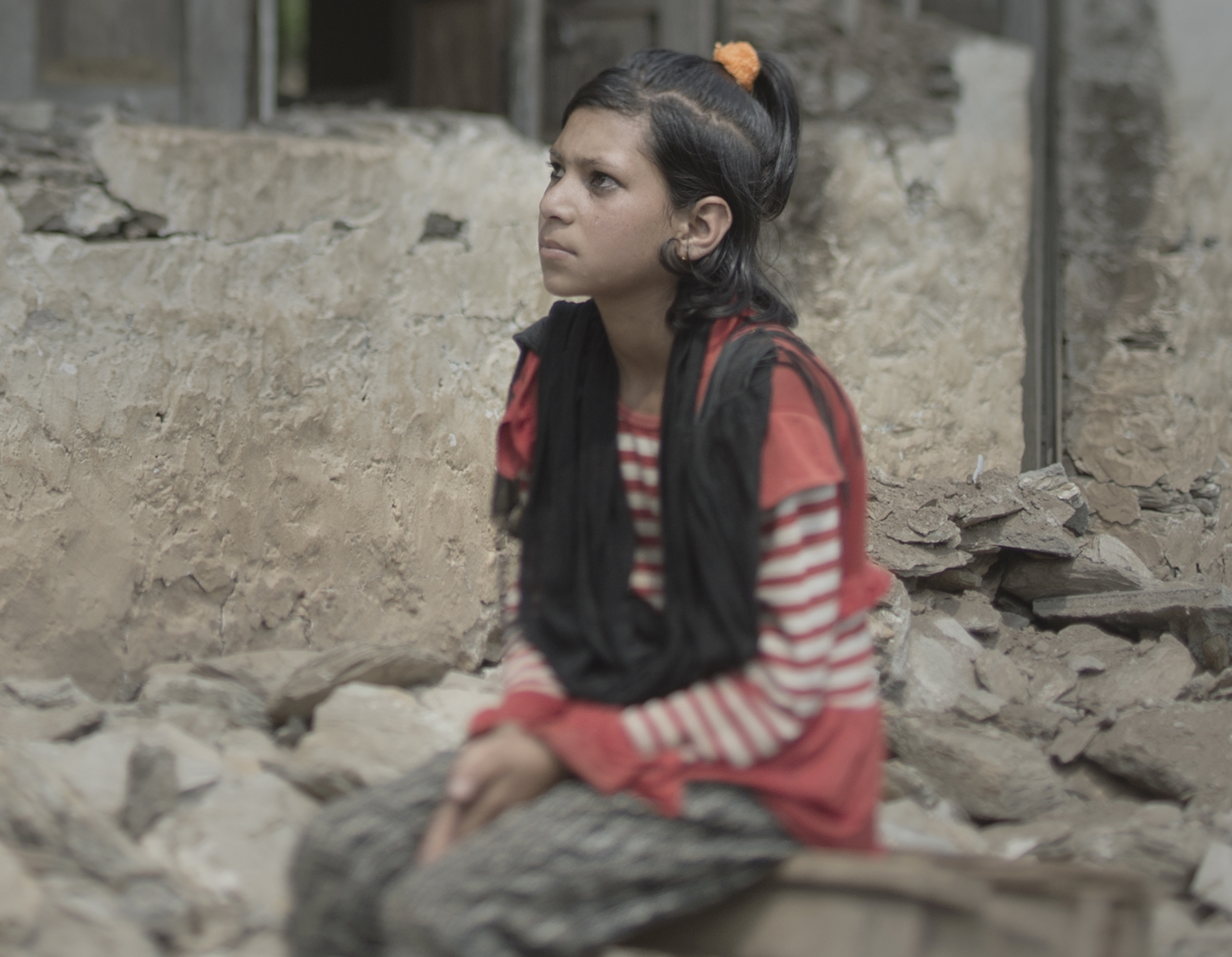 Girl sits by a destroyed house after the Nepal earthquakes