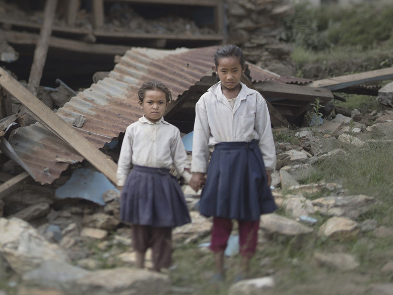 Girls stand among rubble after the Nepal earthquakes