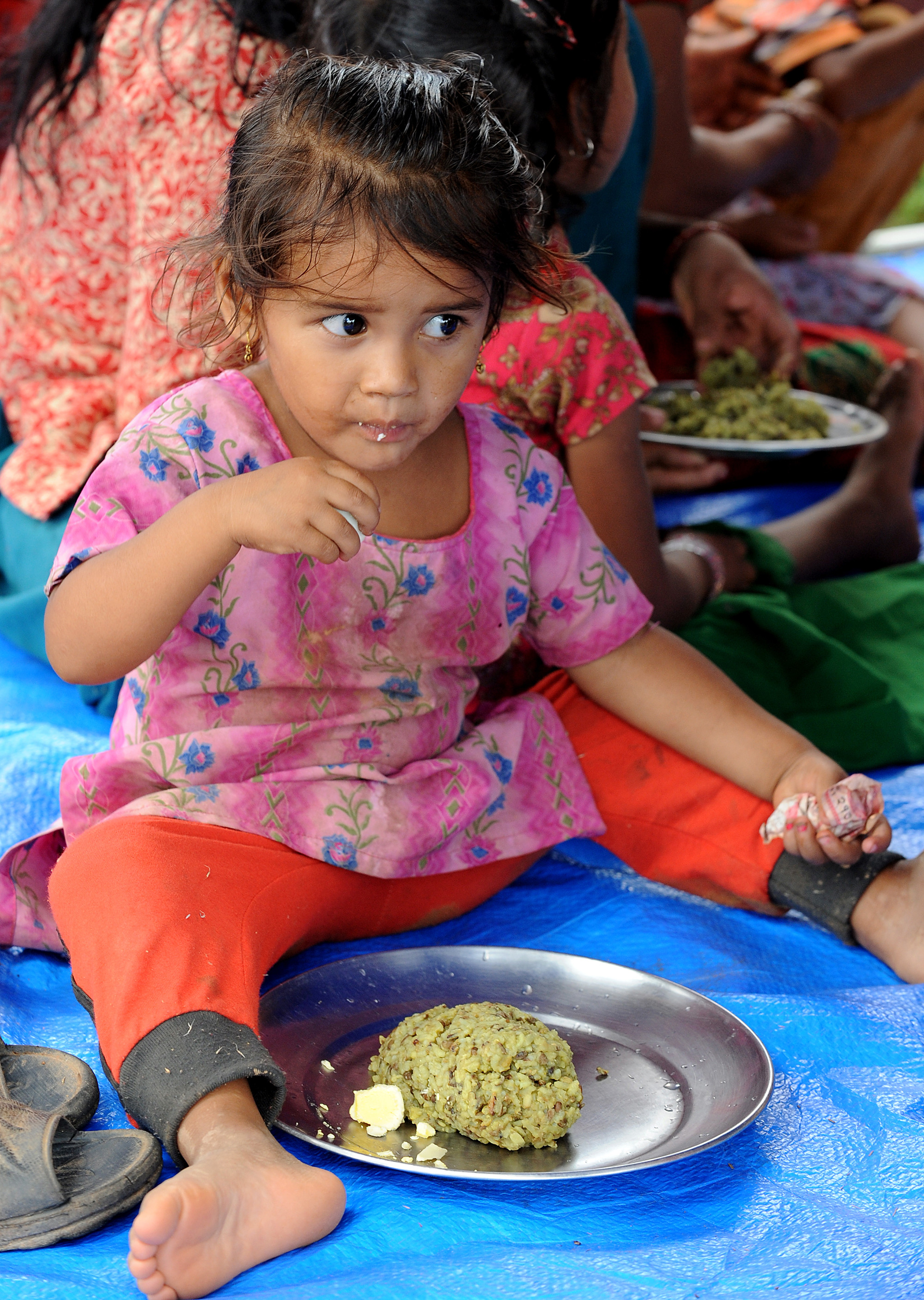 A child eats food provided by a Plan International shelter camp after the Nepal earthquake