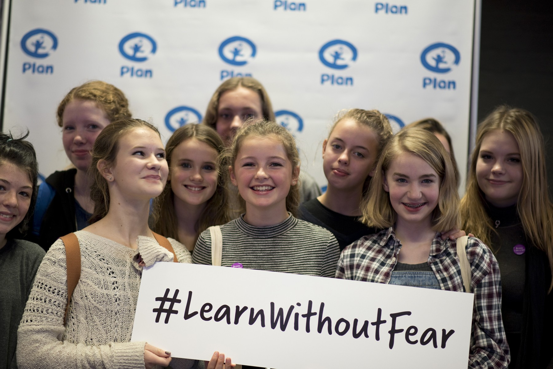 Group hold up a #LearnWithoutFear sign at Youth Action Festival