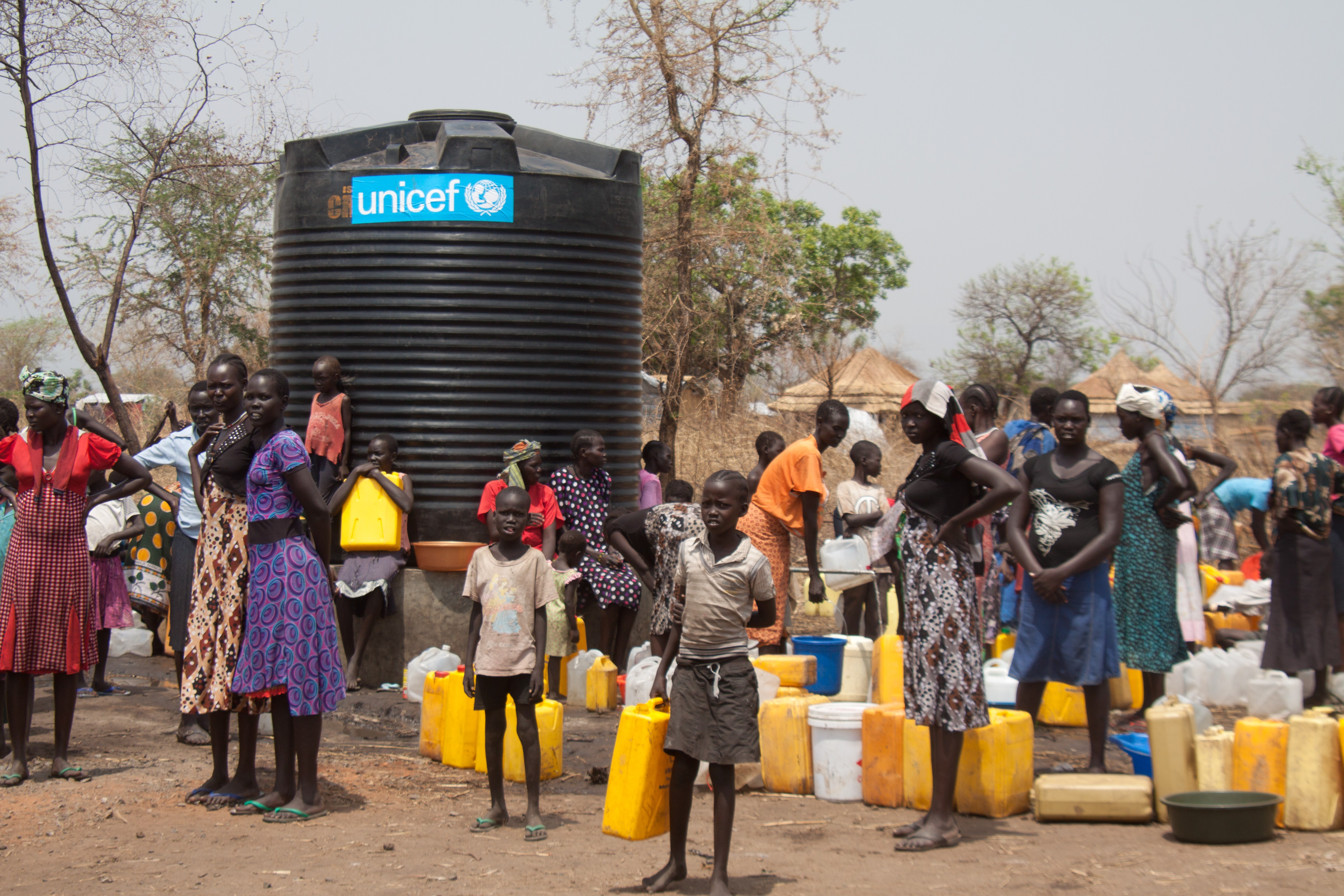 Refugees from South Sudan at a camp in Uganda wait for water