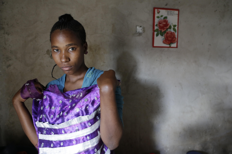 Latfia, a child bride, holds her wedding dress