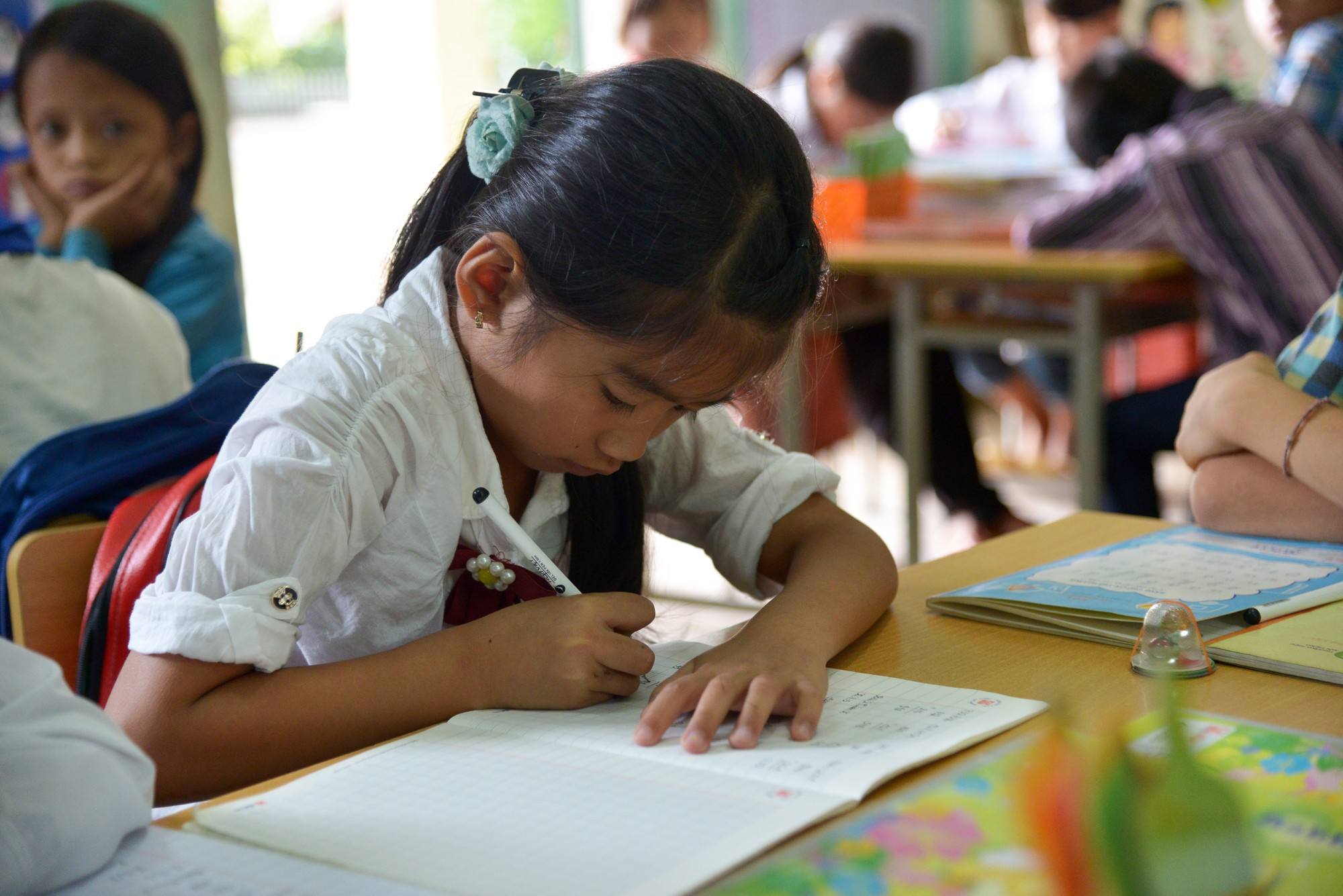 Girl writes in a classroom in Vietnam