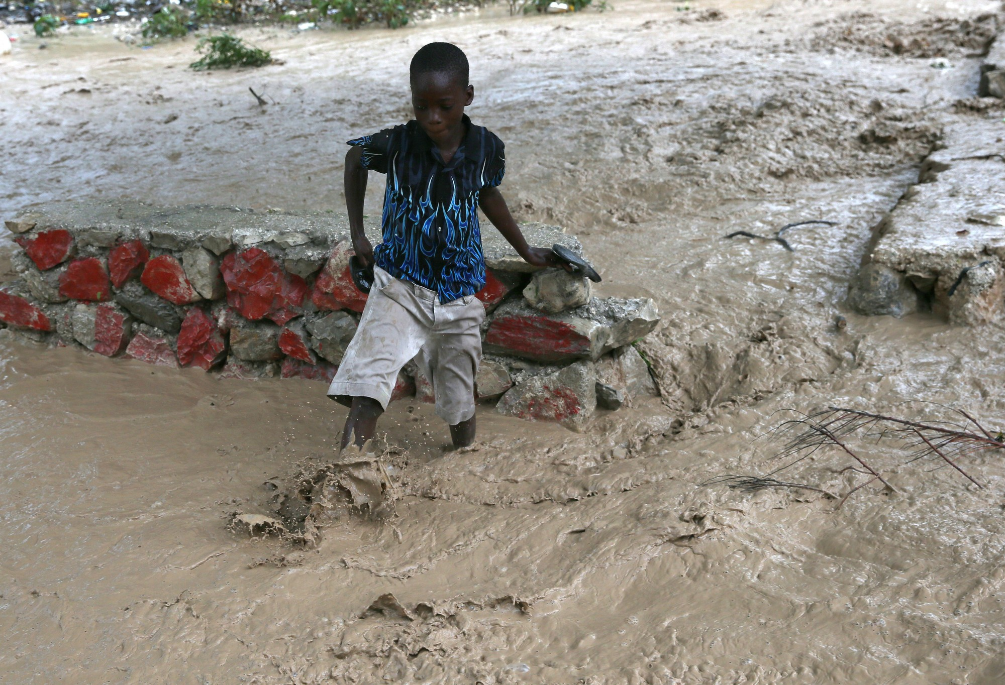 A boy escapes the flood waters caused by hurricane Matthew in Haiti