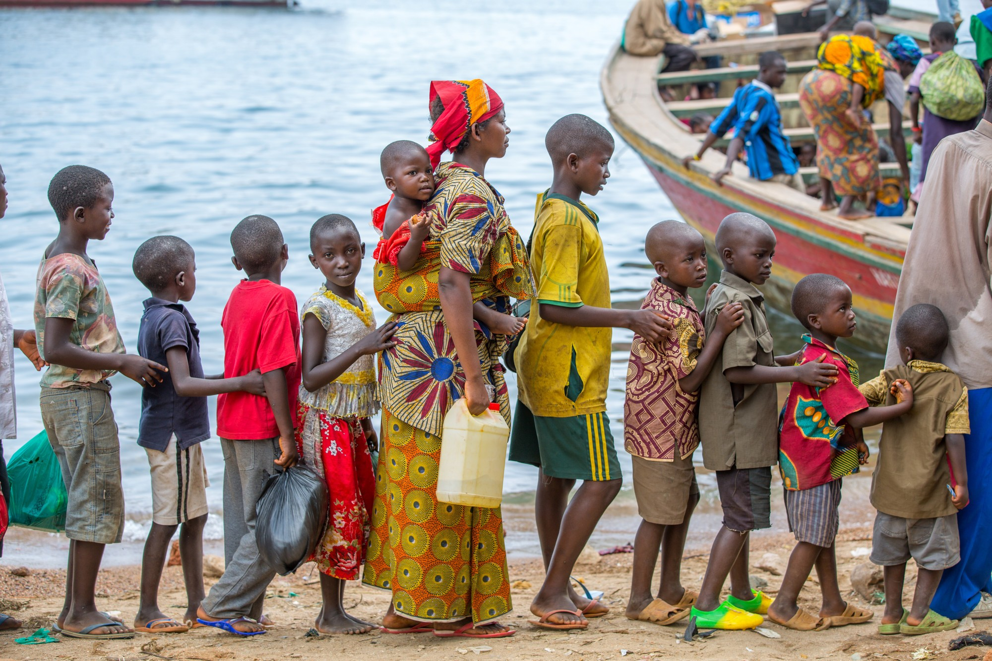 Children queue to board boat in the tiny village of Kagunga