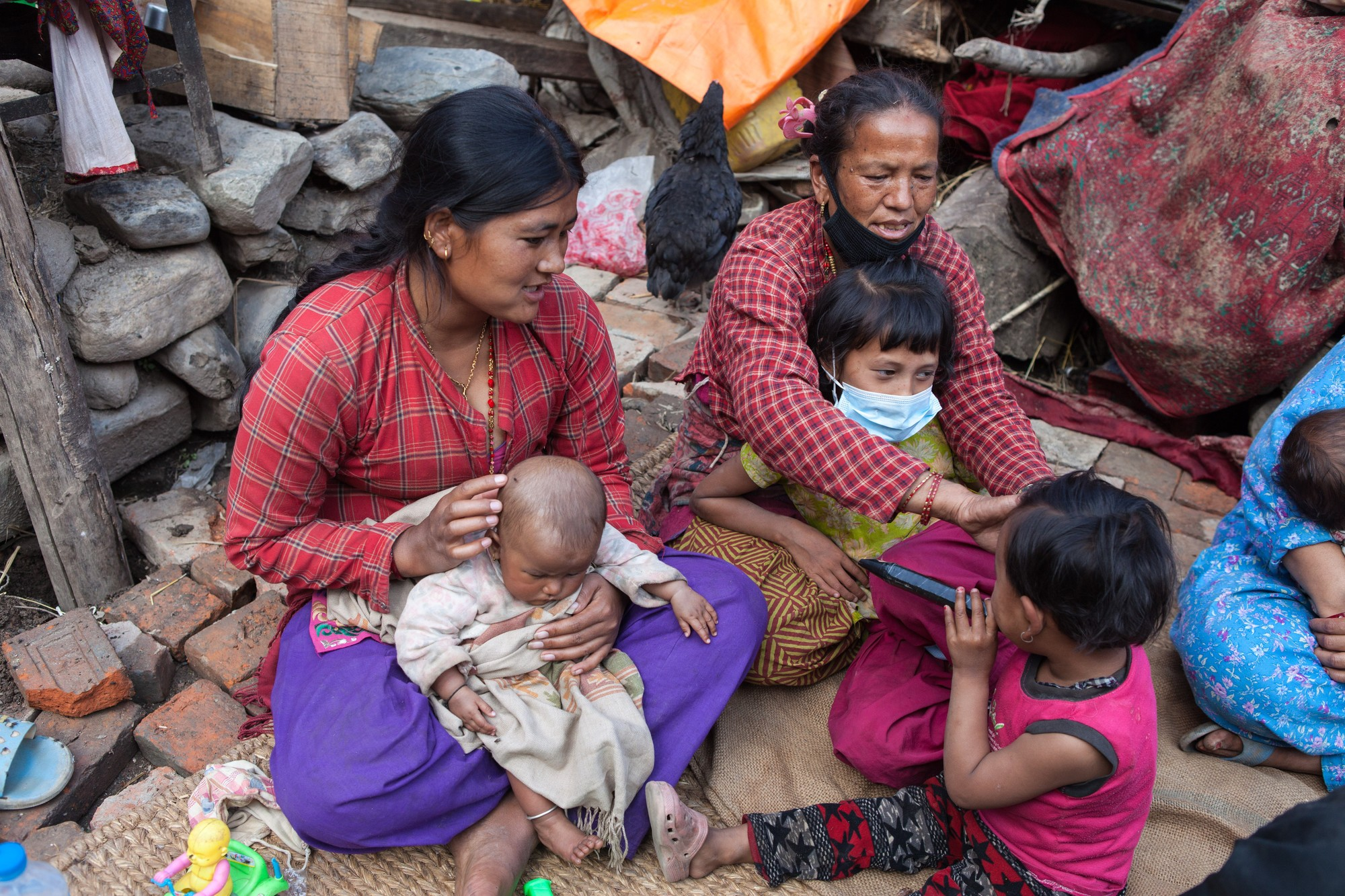 Family sits amid rubble of their home in Sankhu Nepal