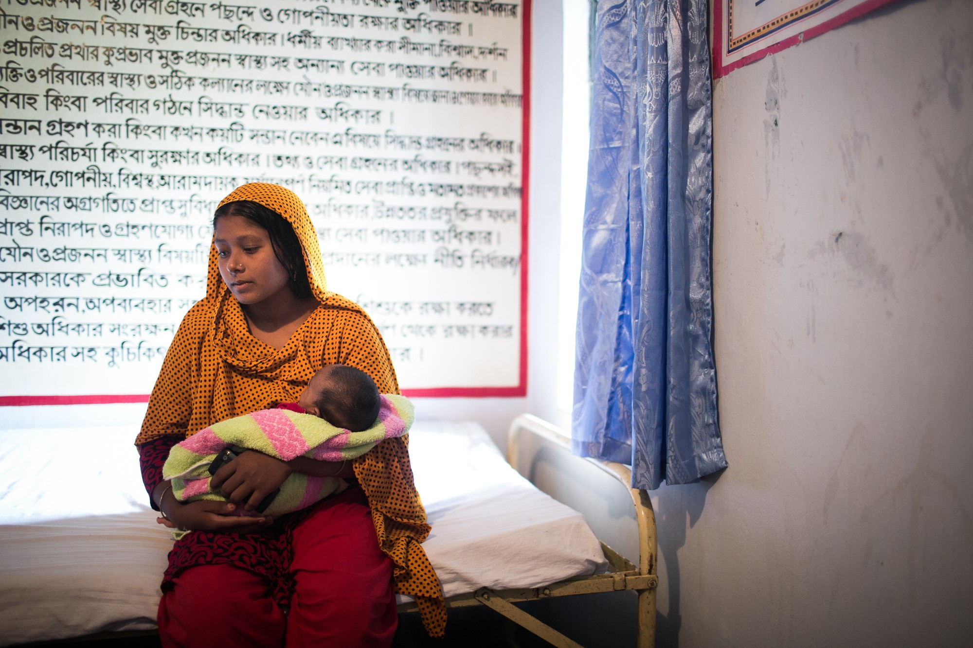 Tohura holding her baby in her arms at her home in Dinajpur region