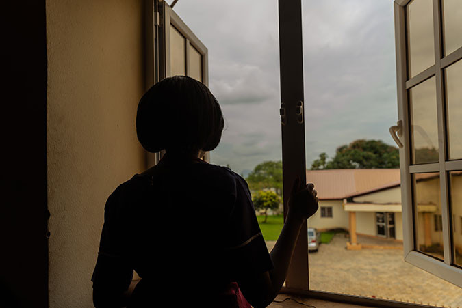 A girl stands at a window