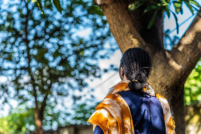 A girl looks up at a tree