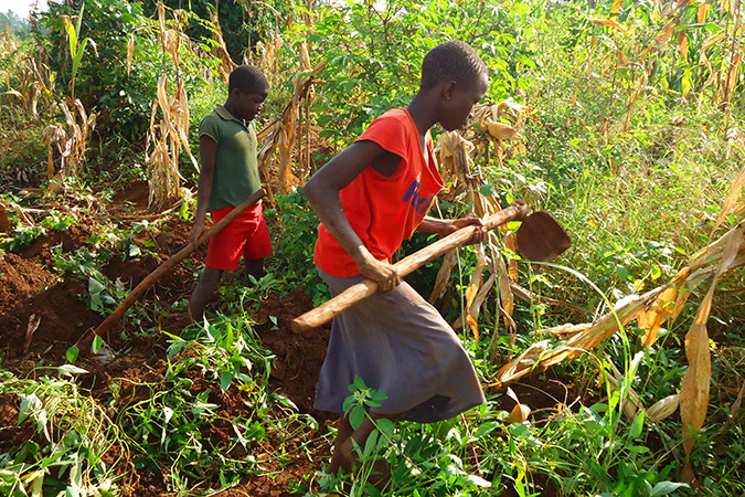 A girl working with her brother in Uganda