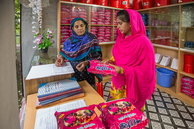 Lucky, left, at her Sanimart in Bangladesh