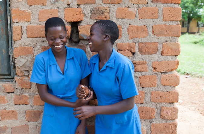 Anna Hope and her friend Everline laugh together at school in Uganda