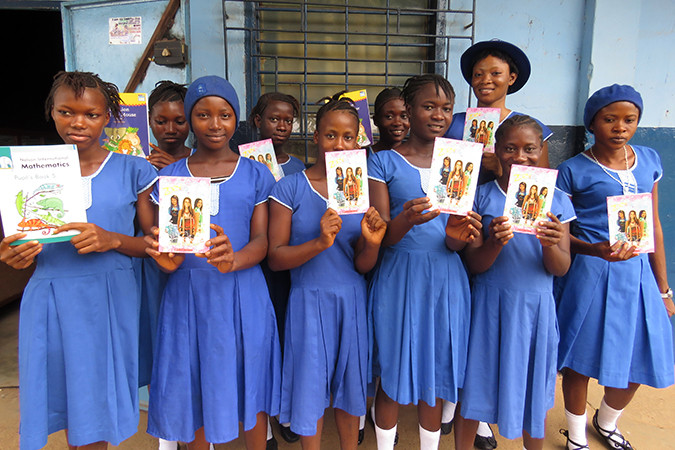 School girls in Sierra Leone with some of the new books delivered to their school.