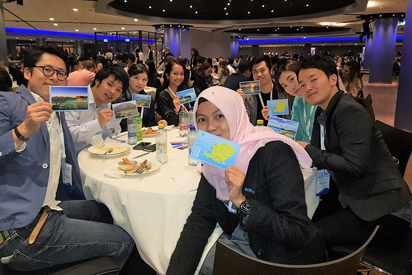 Syifa and other delegates with the postcards she gave out at the One Young World summit