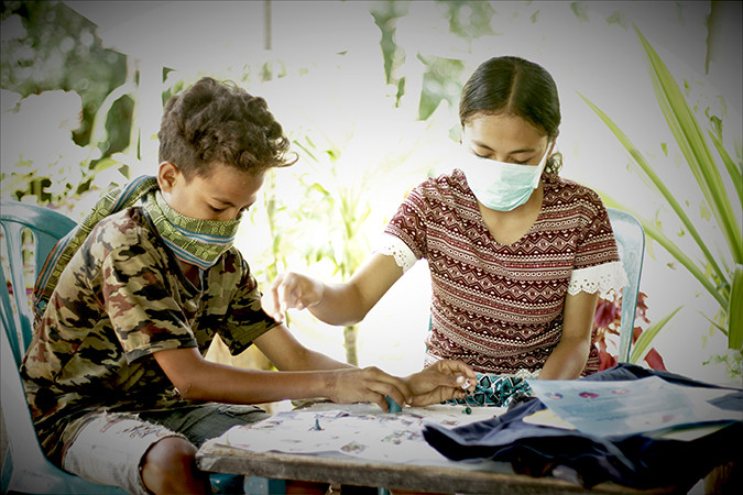 Photo of two children wearing masks playing a game
