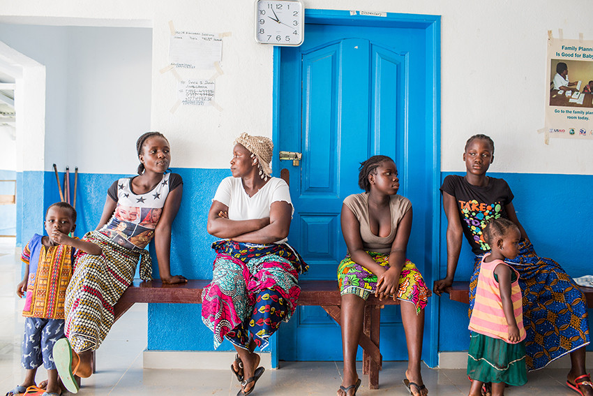 Women wait with their children at a health clinic built by Plan International in Liberia