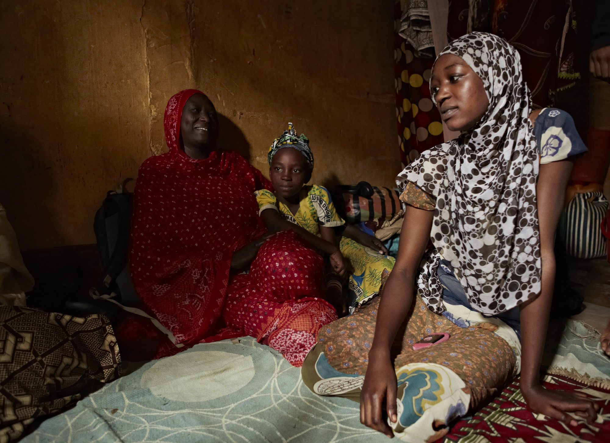Child bride Lamana sits with her family after escaping a violent marriage