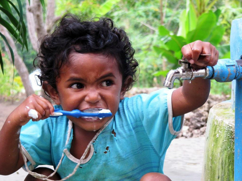 Child brushes teeth at a Plan International installed water pump